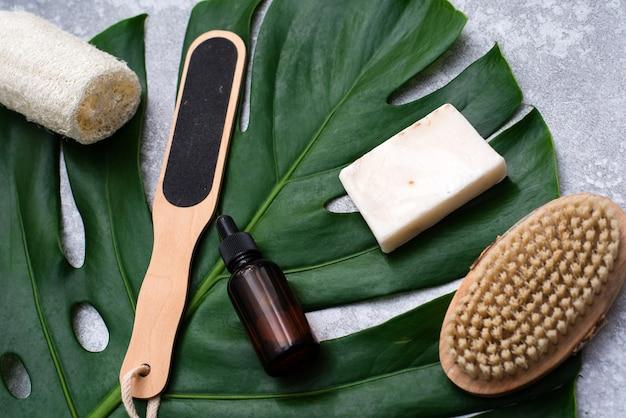 Une belle composition avec de l'huile, du savon et des noix. bouteilles avec produits cosmétiques spa sur fond de feuille de palmier, vue de dessus. concept de procédures de salon de beauté.