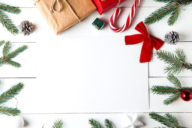 Belle composition de noël sur fond blanc en bois. carte vide avec des boîtes de cadeaux de noël