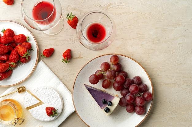 Belle composition avec vue de dessus de gâteau au fromage aux fraises, raisins, fromage et myrtille