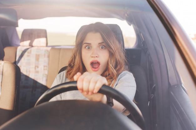 Une belle conductrice européenne choquée se rend compte que sa voiture est cassée, ne peut pas la réparer seule, voit un terrible accident sur la route, a une expression effrayée surprise inattendue. conduite et problèmes