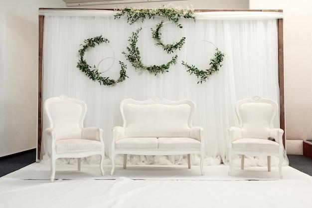 Belle configuration de décoration pour la cérémonie de mariage avec un canapé et des fauteuils blancs classiques