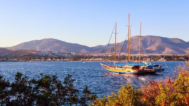 Belle côte méditerranéenne avec des montagnes d'îles et un yacht au coucher du soleil