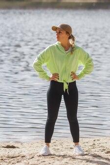 Belle coureuse auto-déterminée dans des vêtements de sport à la mode posant isolée sur l'étirement de la berge de la rivière