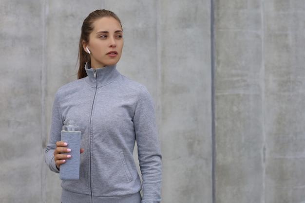 Belle coureuse est debout à l'extérieur tenant une bouteille d'eau. la femme de remise en forme fait une pause après avoir couru l'entraînement.