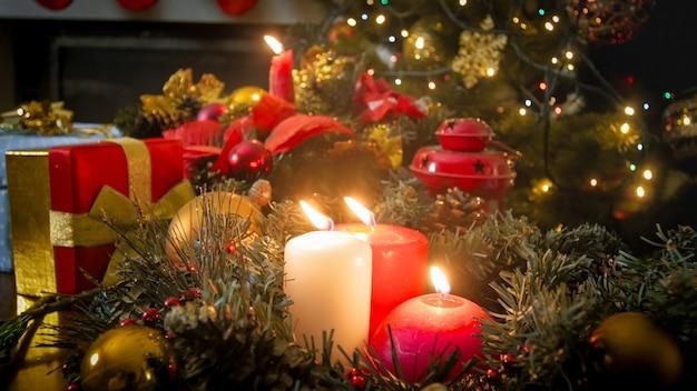 Belle couronne de l'avent avec des bougies allumées contre un sapin de noël décoré