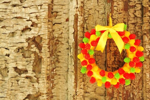 Belle couronne de bonbons accrochée à une vieille porte en bois