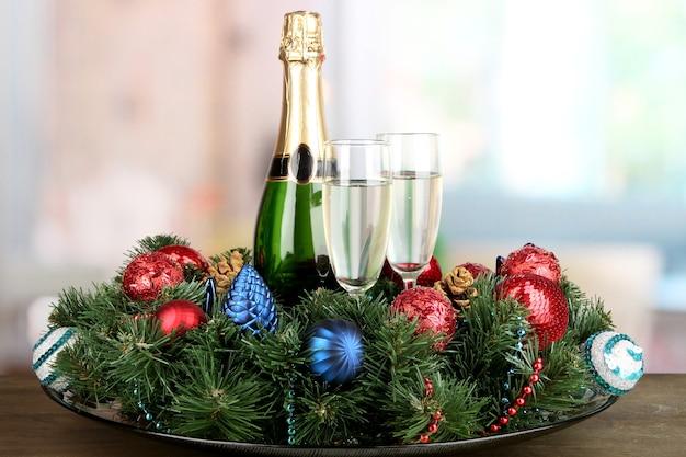 Belle couronne de noël en composition avec champagne sur fond de chambre