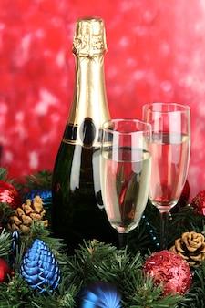 Belle couronne de noël en composition avec champagne sur fond rouge