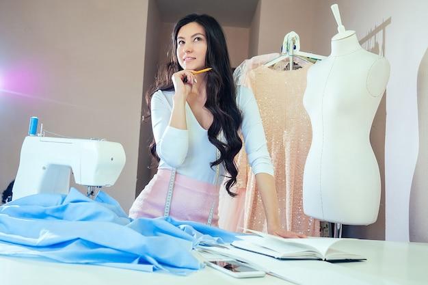 Une belle couturière aux cheveux longs écrit dans un cahier. le tailleur crée une collection de tenues. vêtements de créateurs de jeune femme écrivant des idées dans un cahier. concept de muse, idée et inspiration