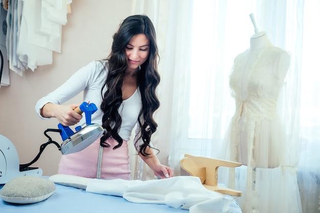 Belle couturière tient dans sa main un fer à repasser électrique. le tailleur coud un costume pour le client. couturière, mannequin et fer à repasser dans l'atelier. traitement thermique humide des vêtements dans le processus de couture.