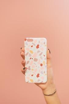 Belle couverture de couleur dans la main de la jeune fille sur un mur pastel rose