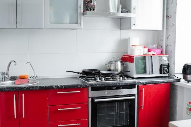 Belle cuisine rouge propre et moderne dans petit appartement full shot