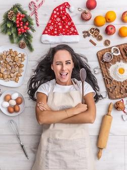 Belle cuisinière aux cheveux noirs clignotant allongée et sur le sol, tenant la cuillère en bois et entourée de pains d'épice, d'œufs, de farine, de chapeau de noël et de fruits.