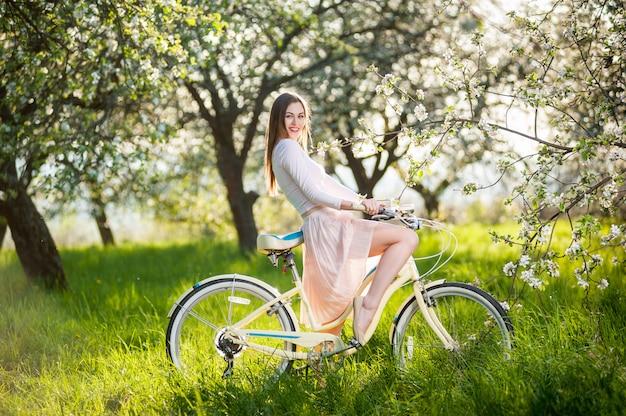 Belle cycliste avec vélo rétro dans le jardin de printemps
