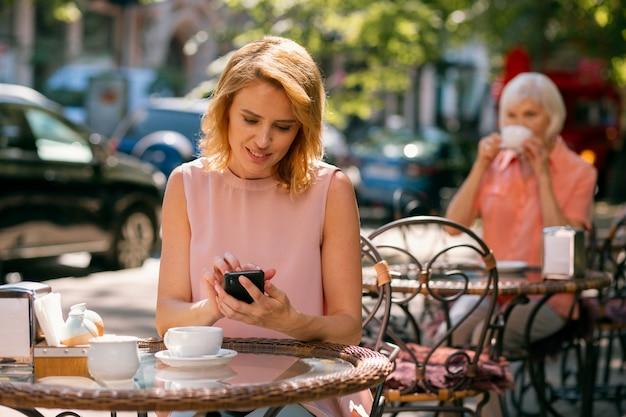 Belle dame adulte souriante assise à la table du café à l'extérieur et regardant l'écran de son smartphone