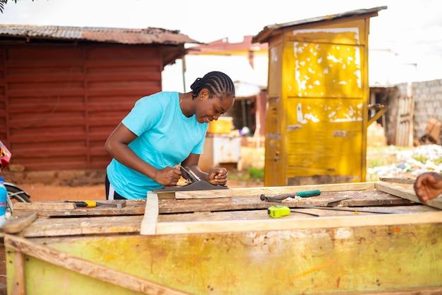 Belle dame africaine sourit alors qu'elle utilise un avion jack pour habiller le bois en taille