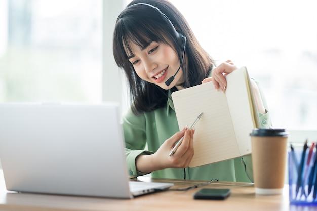 Belle dame asiatique du service client appelle les clients pour offrir des produits