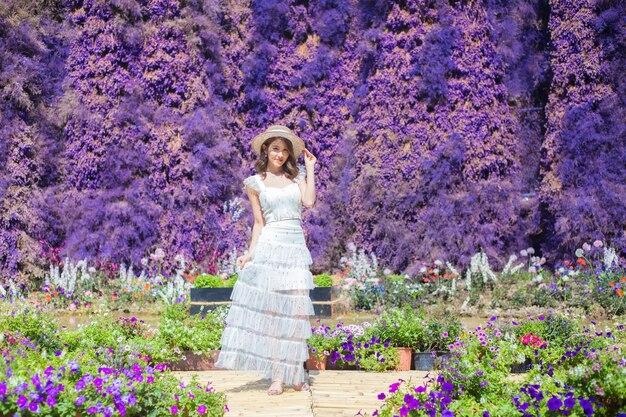 Une belle dame asiatique qui porte une robe blanche et un chapeau se dresse au milieu d'un jardin de fleurs violettes