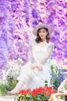 Belle dame asiatique en robe blanche porte un chapeau blanc et s'assoit au milieu du jardin de fleurs violettes avec bonheur