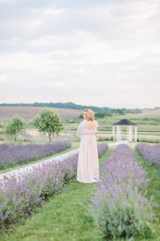 Belle dame blonde magnifique d'âge moyen en robe élégante marchant dans le champ de lavande.