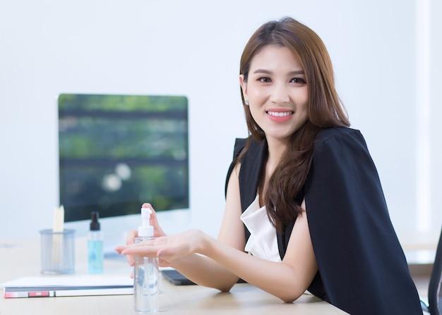 Une belle dame de bureau est assise et appuie sur un gel d'alcool pour se laver les mains au travail.