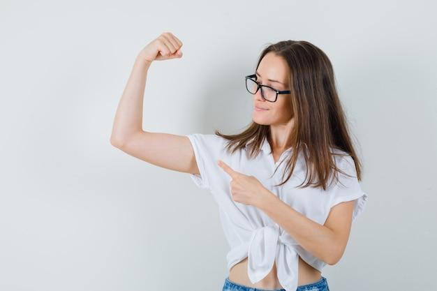 Belle dame en chemisier blanc, lunettes pointant sur les muscles des bras et regardant confiant, vue de face.