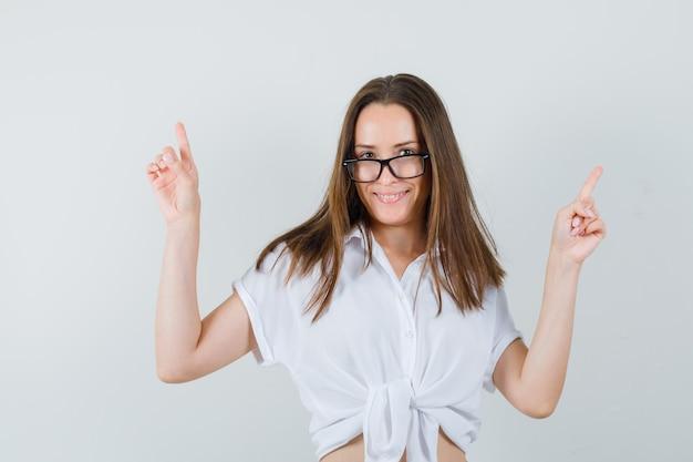 Belle dame en chemisier blanc, lunettes pointant vers le haut et à la vue de face, heureux.