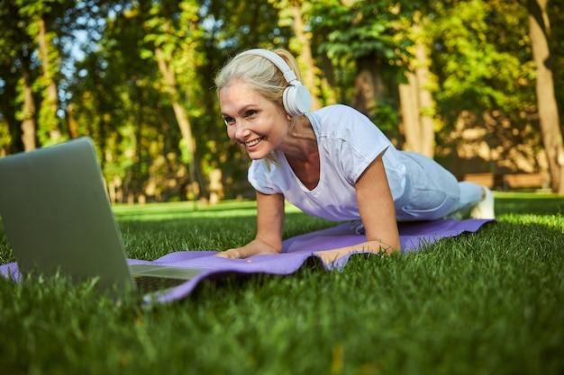 Belle dame dans des écouteurs sans fil faisant de l'exercice et souriant tout en regardant une formation en ligne sur un ordinateur portable à l'extérieur