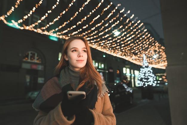 Belle dame dans des vêtements chauds se tient avec un smartphone dans ses mains à l'arrière-plan d'une rue de nuit