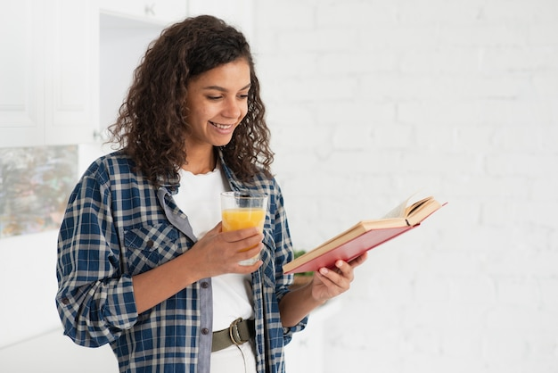 Belle dame lisant un livre et tenant un verre de jus