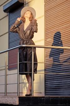 Belle dame en long manteau fourmi manteau vintage debout sur balcon