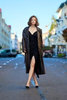 Belle dame en long manteau vintage et robe de soirée au milieu de la route tôt le matin