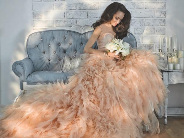 Belle dame en magnifique couture couture sur sofa