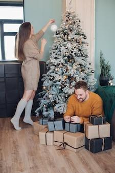 Belle dame mettant des ornements sur l'arbre de noël tout en prenant soin de l'homme emballant des cadeaux