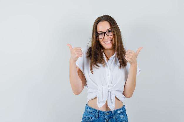 Belle dame montrant le pouce vers le haut en chemisier blanc, lunettes et regardant joyeux, vue de face.