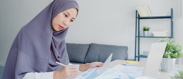 Belle dame musulmane d'asie en tenue décontractée avec foulard utilisant un ordinateur portable dans le salon de la maison.