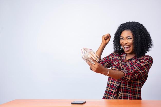 Belle dame noire tenant de l'argent se sentant excitée et heureuse