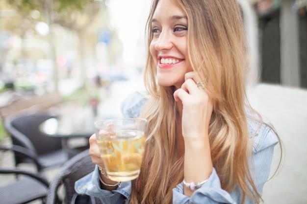 Belle dame parlant au téléphone et boire du thé