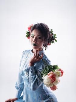 La belle dame avec une pince à cheveux fleurie sur la tête, tenant un bouquet de roses à la main