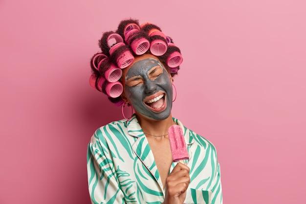 Belle dame portant un masque pour les soins du visage portant des bigoudis isolés