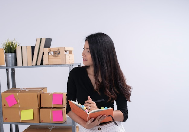 Belle dame en position debout à côté de l'étagère de la boîte aux lettres, vérifier l'ordre et l'écriture sur le livre, se préparer à l'emballage, travailler le commerce électronique, femme d'affaires