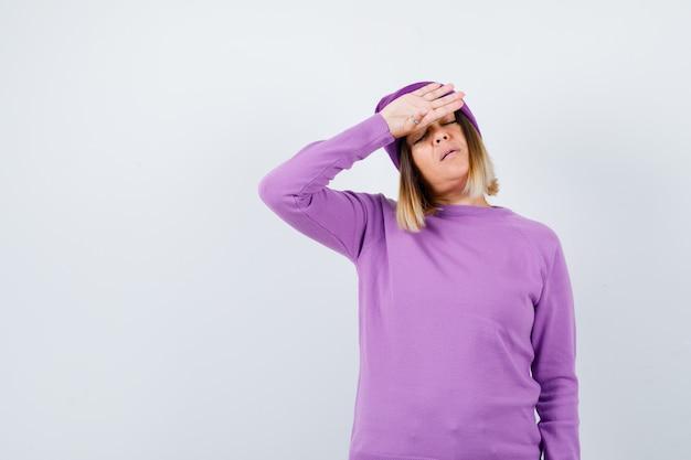 Belle dame en pull, bonnet gardant la main sur le front et l'air fatigué, vue de face.