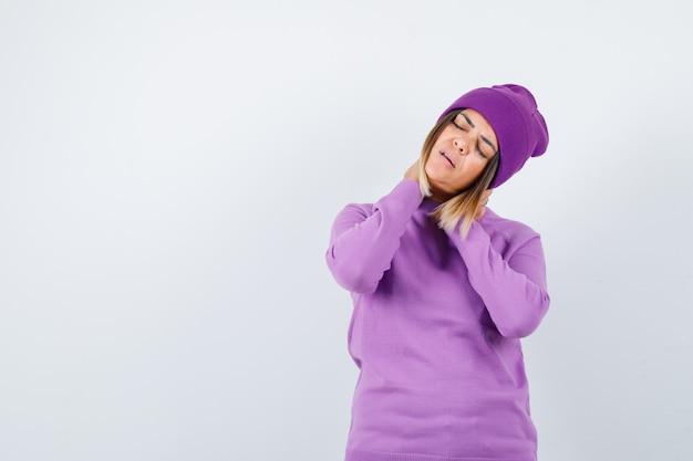 Belle dame en pull, bonnet avec les mains sur le cou et l'air fatigué, vue de face.