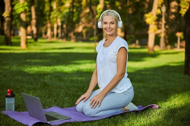 Belle dame regardant la caméra et souriante assise sur un tapis de yoga avec un cahier moderne
