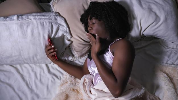 La belle dame regarde l'affichage et les bâillements modernes de smartphone