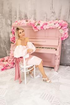 Belle dame en robe rose et piano rose. photo de haute qualité