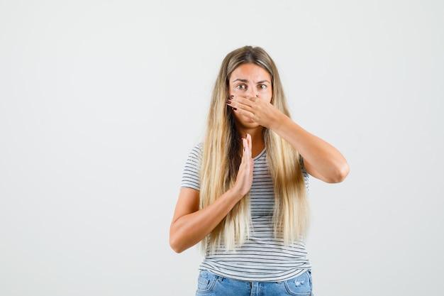 Belle dame se pinçant le nez en raison de la mauvaise odeur du t-shirt et de l'air dégoûté. vue de face.