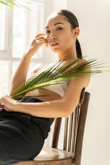 Belle dame se reposant avec une feuille de palmier dans la chambre