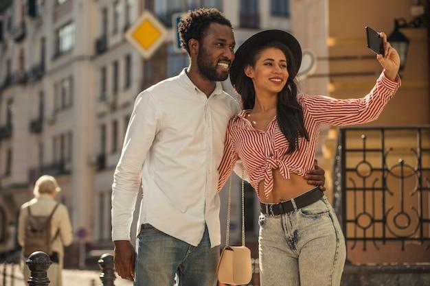 Belle dame souriante dans un chapeau noir debout dans la rue et serrant son amie dans ses bras tout en prenant un selfie avec lui