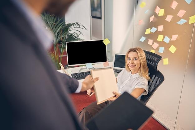 Belle dame souriante remettant un carnet de croquis en spirale à un collègue assis à la table avec un ordinateur et un ordinateur portable au bureau
